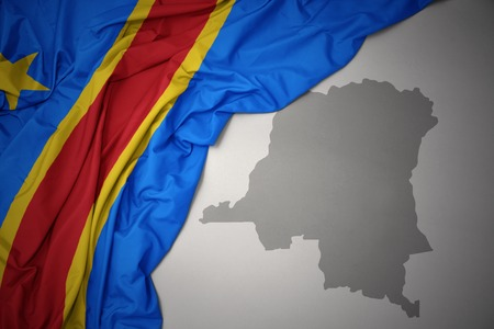 waving colorful national flag of democratic republic of the congo on a gray map background. 3D illustration