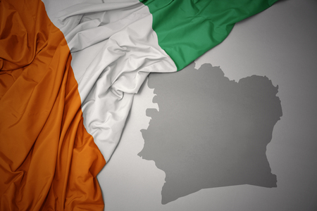 waving colorful national flag of cote divoire on a gray map background. 3D illustration Stock Photo