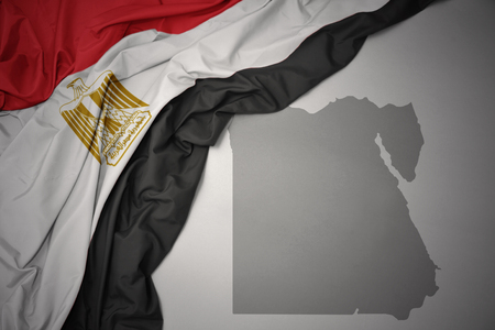 waving colorful national flag of egypt on a gray map background. 3D illustration