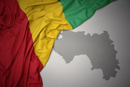 waving colorful national flag of guinea on a gray map background. 3D illustration