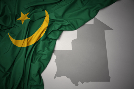 waving colorful national flag of mauritania on a gray map background. 3D illustration