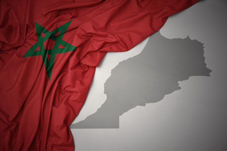 waving colorful national flag of morocco on a gray map background. 3D illustration Stock Photo