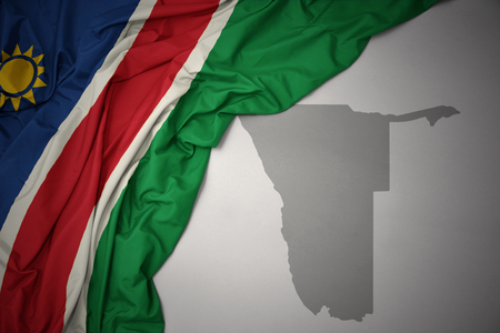 waving colorful national flag of namibia on a gray map background. 3D illustration