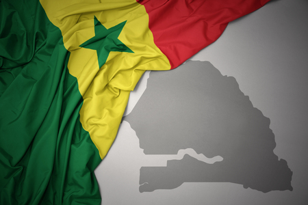 waving colorful national flag of senegal on a gray map background. 3D illustration