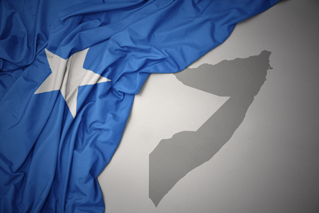 waving colorful national flag of somalia on a gray map background. 3D illustration Stock Photo