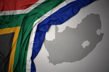 waving colorful national flag of south africa on a gray map background. 3D illustration