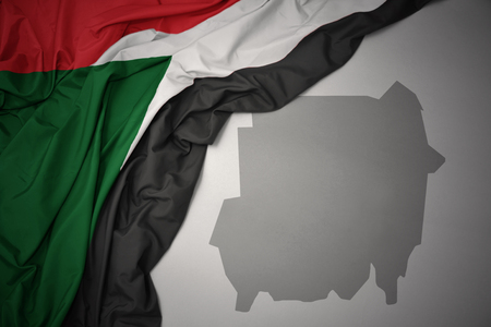 waving colorful national flag of sudan on a gray map background. 3D illustration