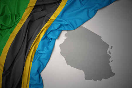 waving colorful national flag of tanzania on a gray map background. 3D illustration