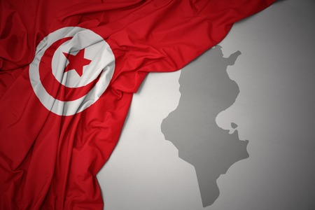 waving colorful national flag of tunisia on a gray map background. 3D illustration