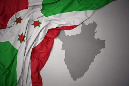 waving colorful national flag of burundi on a gray map background. 3D illustration Stock Photo
