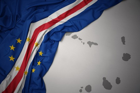 waving colorful national flag of cape verde on a gray map background. 3D illustration Stock Photo