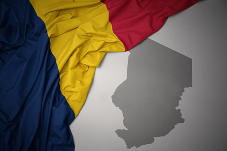 waving colorful national flag of chad on a gray map background. 3D illustration