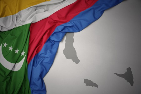 waving colorful national flag of comoros on a gray map background. 3D illustration