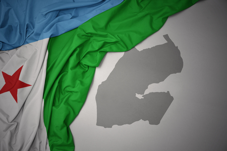 waving colorful national flag of djibouti on a gray map background. 3D illustration Stock Photo
