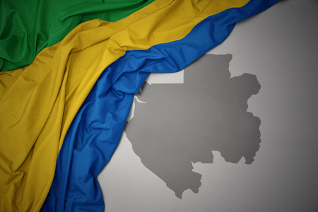 waving colorful national flag of gabon on a gray map background. 3D illustration