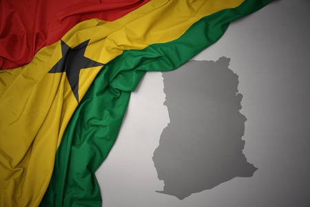waving colorful national flag of ghana on a gray map background. 3D illustration