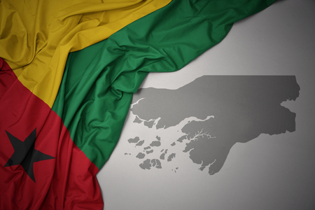 waving colorful national flag of guinea bissau on a gray map background. 3D illustration Stock Photo