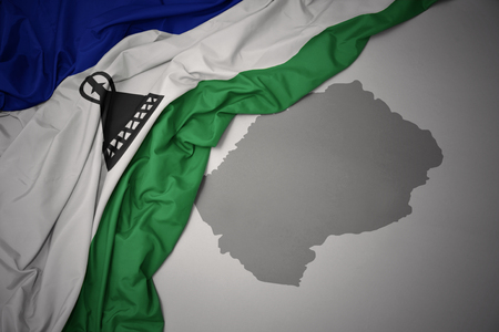 waving colorful national flag of lesotho on a gray map background. 3D illustration