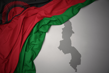waving colorful national flag of malawi on a gray map background. 3D illustration