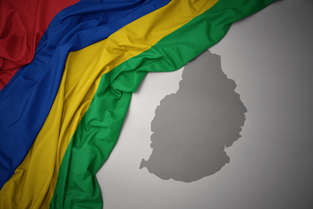 waving colorful national flag of mauritius on a gray map background. 3D illustration