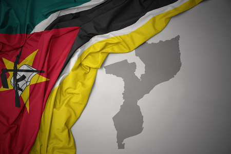 waving colorful national flag of mozambique on a gray map background. 3D illustration