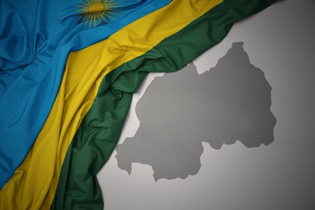 waving colorful national flag of rwanda on a gray map background. 3D illustration Stock Photo