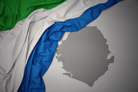 waving colorful national flag of sierra leone on a gray map background. 3D illustration