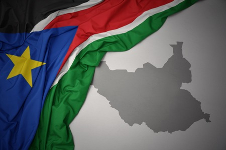 waving colorful national flag of south sudan on a gray map background. 3D illustration