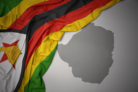 waving colorful national flag of zimbabwe on a gray map background. 3D illustration Stock Photo