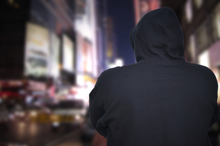 dangerous man standing on a city street at night with black hoodie