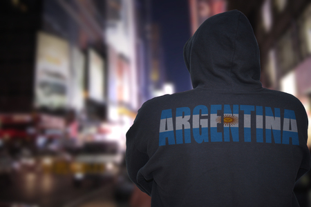 dangerous man standing on a city street at night with black hoodie with text argentina on his back