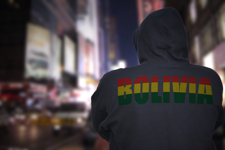 dangerous man standing on a city street at night with black hoodie with text bolivia on his back Stock Photo