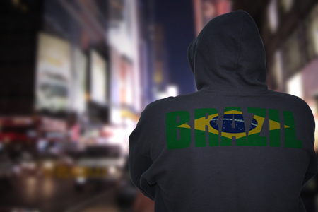 dangerous man standing on a city street at night with black hoodie with text brazil on his back