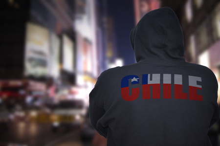 dangerous man standing on a city street at night with black hoodie with text chile on his back