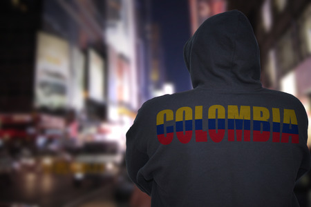 dangerous man standing on a city street at night with black hoodie with text colombia on his back