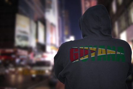 dangerous man standing on a city street at night with black hoodie with text guyana on his back