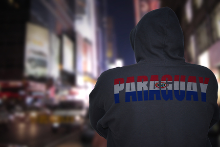 dangerous man standing on a city street at night with black hoodie with text paraguay on his back
