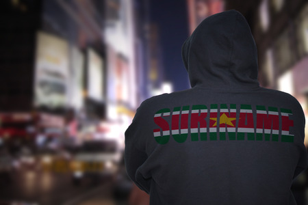 dangerous man standing on a city street at night with black hoodie with text suriname on his back Фото со стока