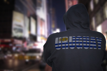 dangerous man standing on a city street at night with black hoodie with text uruguay on his back Stock Photo