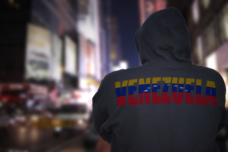 dangerous man standing on a city street at night with black hoodie with text venezuela on his back Stock Photo