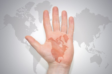 hand with map of northern america on the gray world map background. concept Stock Photo
