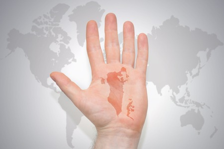 hand with map of bahrain on the gray world map background. concept