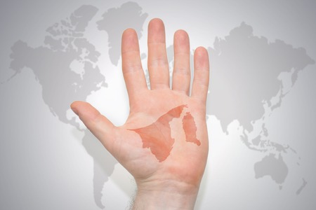 hand with map of brunei on the gray world map background. concept