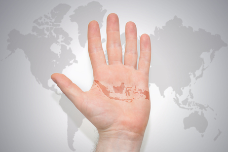 hand with map of indonesia on the gray world map background. concept