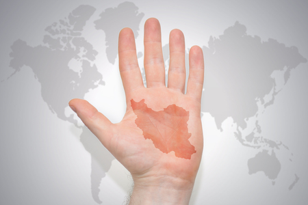 hand with map of iran on the gray world map background. concept