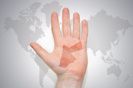 hand with map of jordan on the gray world map background. concept