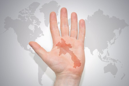 hand with map of laos on the gray world map background. concept Stock Photo