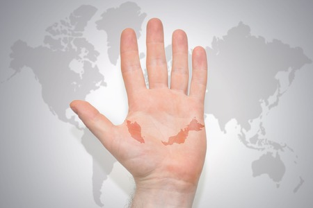 hand with map of malaysia on the gray world map background. concept Stock Photo