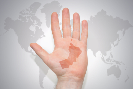 hand with map of oman on the gray world map background. concept