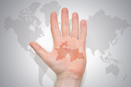 hand with map of tajikistan on the gray world map background. concept Stock Photo